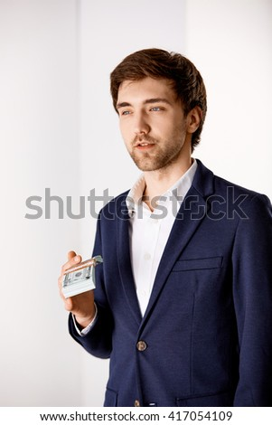 Portrait of a handsome young businessman in suit holding money looking away thinking. - stock photo