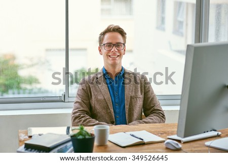 Portrait of a handsome young businessman laughing confidently while sitting comfortably behind his desk  - stock photo