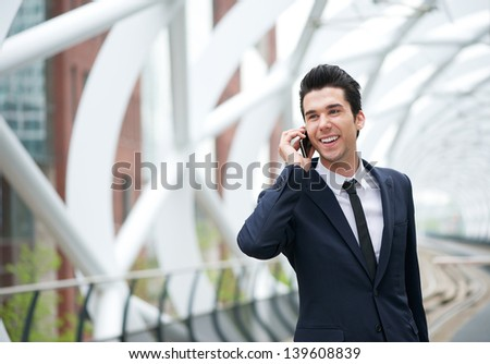 Portrait of a handsome young businessman on the phone at station - stock photo
