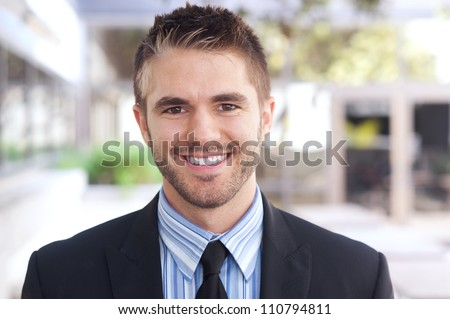 portrait of a handsome young businessman standing outside office - stock photo