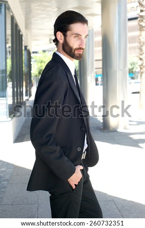 Portrait of a handsome young businessman walking outside in business suit - stock photo