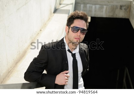 Portrait of a handsome young businessman with sunglasses - stock photo