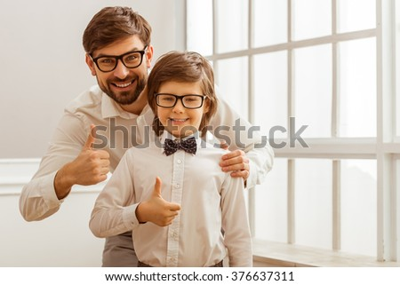 Portrait of a handsome young father and his cute little son in a bow tie. Both in white classical shirts and eyeglasses, showing OK sign, looking in camera and smiling - stock photo
