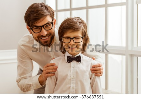Portrait of a handsome young father and his cute little son in a bow tie. Both in white classical shirts and eyeglasses, looking in camera and smiling - stock photo