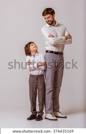 Portrait of a handsome young father and his cute little son standing back to back, looking at each other and smiling. Both in white classical shirts and gray pants, standing on a gray background. - stock photo