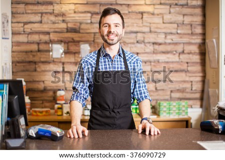 Portrait of a handsome young Hispanic business owner standing at the checkout counter and smiling - stock photo