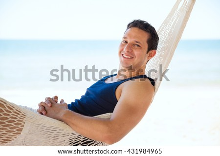 Portrait of a handsome young Hispanic man enjoying his vacation at the beach and laying on a hammock - stock photo