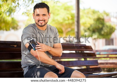 Portrait of a handsome young Hispanic man exercising outdoors in a park and listening to music with a smartphone and armband