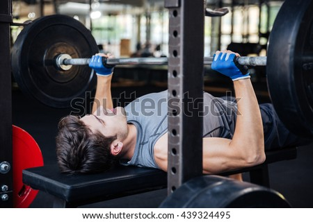 Portrait of a handsome young male bodybuilder doing bench press in gym