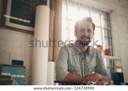 Portrait of a handsome young male designer looking positively at the camera with gentle sun flare coming in through the window of his studio - stock photo
