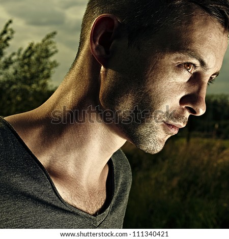 portrait of a handsome young man against a background nature - stock photo