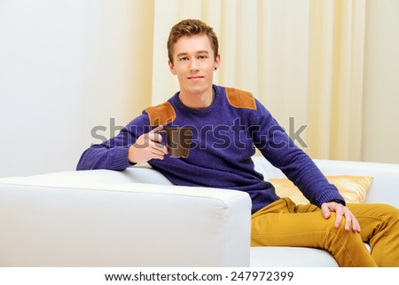 Portrait of a handsome young man at home, drinking tea or coffee and smiling at camera. - stock photo