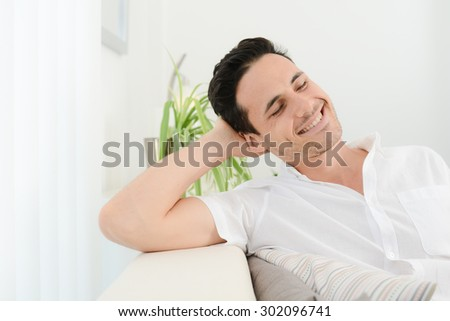 portrait of a handsome young man at home in bright white background - stock photo