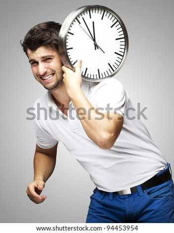 portrait of a handsome young man carrying a clock against a grey - stock photo