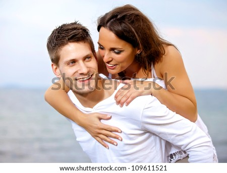 Portrait of a handsome young man carrying his girlfriend on his back - stock photo