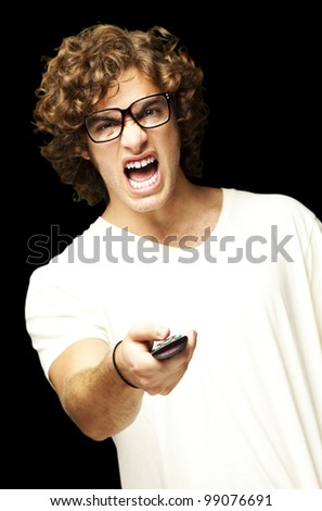 portrait of a handsome young man changing channel against a black background - stock photo