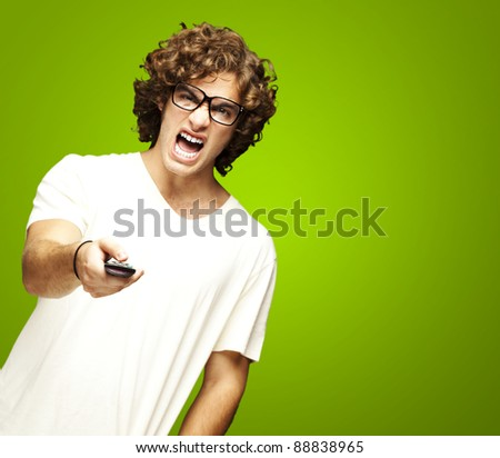 portrait of a handsome young man changing channel against a green background - stock photo
