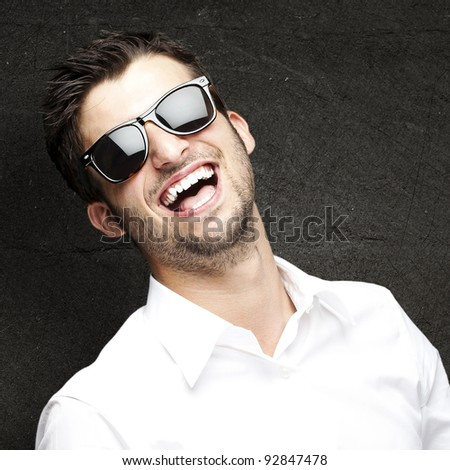 portrait of a handsome young man enjoying against a grunge wall