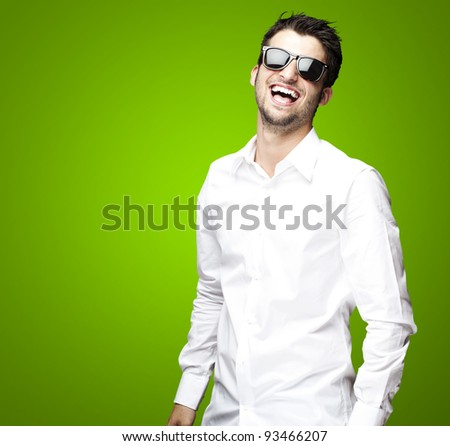portrait of a handsome young man enjoying over green background - stock photo