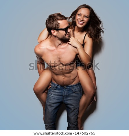 Portrait of a handsome young man giving a piggyback ride to his girlfriend - stock photo