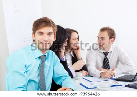portrait of a handsome young man happy smile. Sitting at the desk at office with business colleagues people in the background businesspeople working, businessman looking at camera,