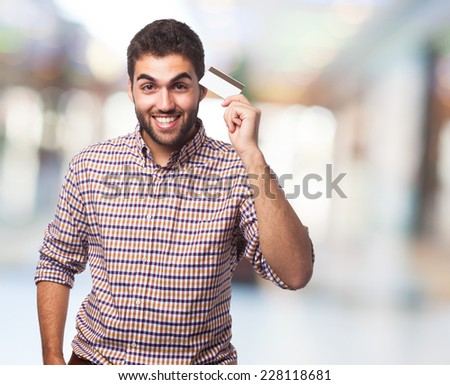 portrait of a handsome young man holding a credit card - stock photo