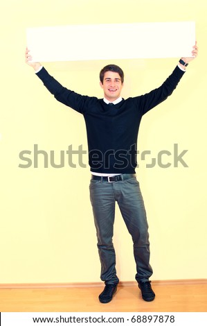 Portrait of a handsome young man holding empty sheet over head against uniform background - stock photo