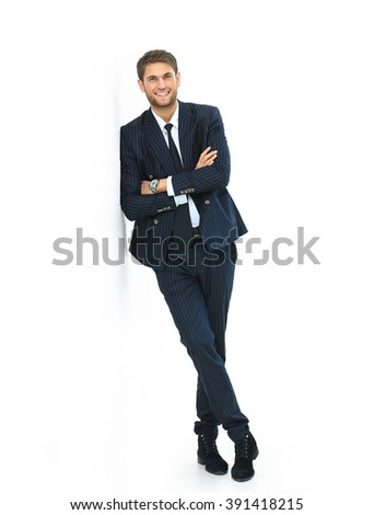 Portrait of a handsome young man in a business suit. standing near the wall - stock photo