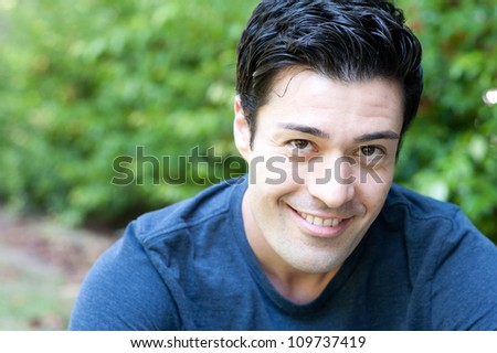 portrait of a handsome young man in a park - stock photo