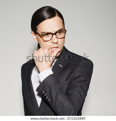 Portrait of a handsome young man in a studio in a suit and glasses - stock photo