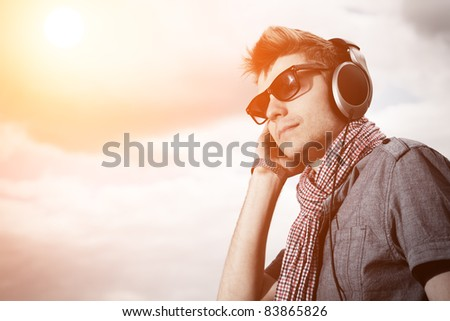 Portrait of a handsome young man in headphones posing outdoor. - stock photo