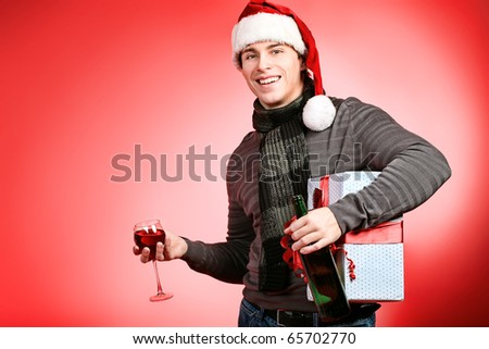 Portrait of a handsome young man in Santa Claus hat celebrating Christmas. - stock photo