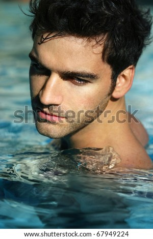Portrait of a handsome young man in swimming pool - stock photo