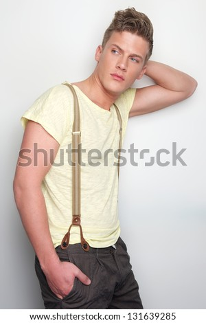Portrait of a handsome young man leaning against wall - stock photo