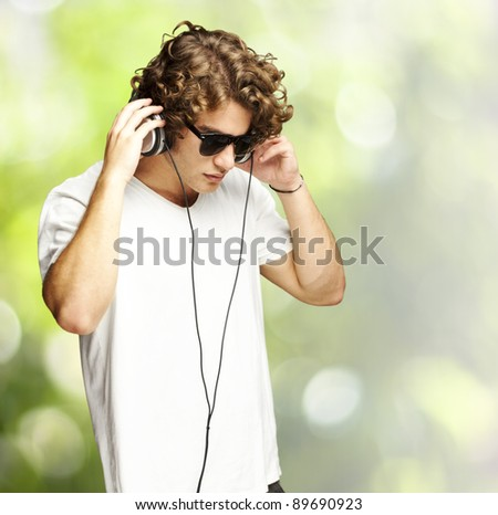 portrait of a handsome young man listening music against a nature background