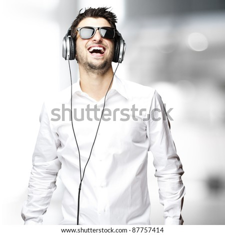 portrait of a handsome young man listening music indoor - stock photo