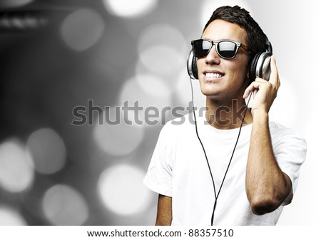 portrait of a handsome young man listening to music against a abstract background - stock photo