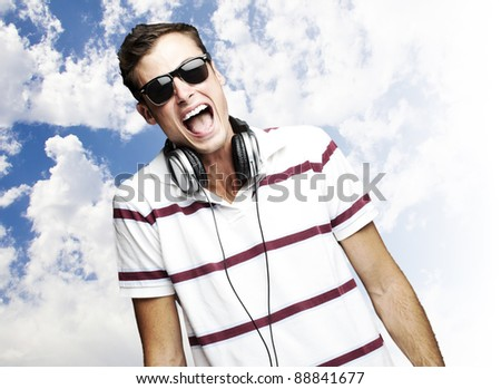 portrait of a handsome young man listening to music against a cloudy sky - stock photo