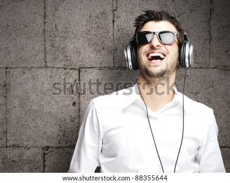 portrait of a handsome young man listening to music against a grunge bricks wall