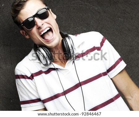 portrait of a handsome young man listening to music against a vintage wall - stock photo