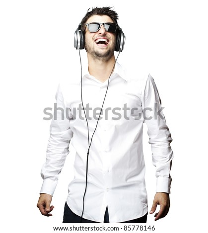 portrait of a handsome young man listening to music with headphones over white - stock photo