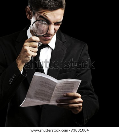 portrait of a handsome young man looking at a contract against a black background - stock photo