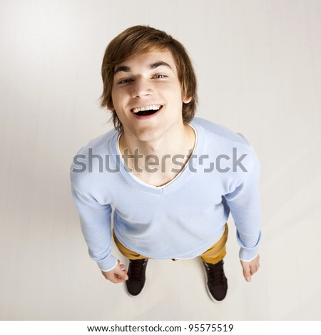 Portrait of a handsome young man looking up and laughing - stock photo