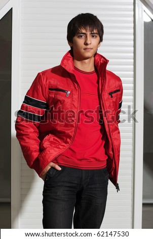 Portrait of a handsome young man of sixteen. Youth shows autumn, winter clothing. - stock photo
