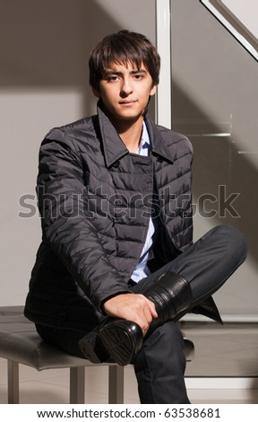 Portrait of a handsome young man of sixteen. Youth shows autumn, winter clothing.