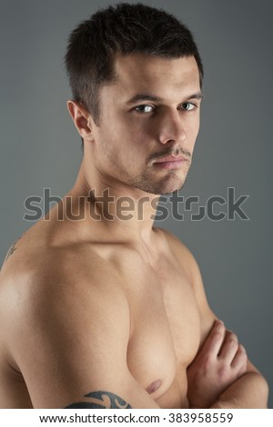 Portrait of a handsome, young man on a gray background, side view. - stock photo