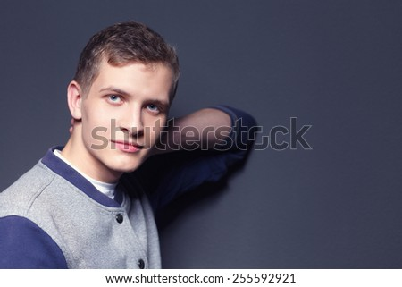 Portrait of a handsome young man on black background - stock photo