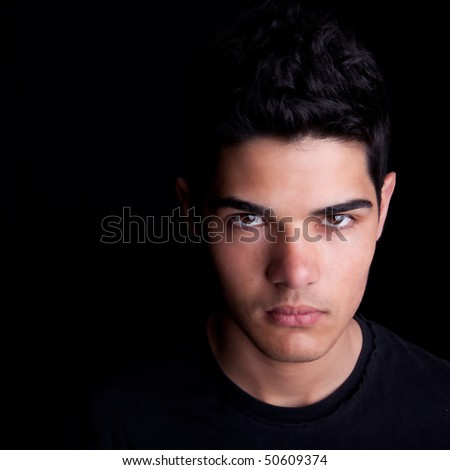 Portrait of a handsome young man on black background. Studio shot. - stock photo
