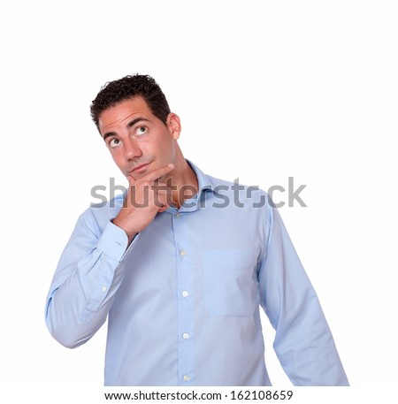 Portrait of a handsome young man on blue shirt with pensive gesture standing on isolated background - copyspace