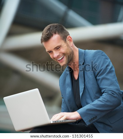 Portrait of a handsome young man on laptop outdoors - stock photo